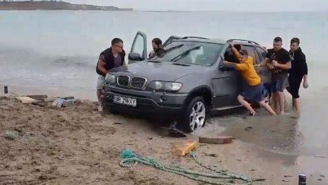BMW X5 la apă! Un șofer teribilist a vrut să-și facă selfie cu mașina pe plajă și a rămas blocat